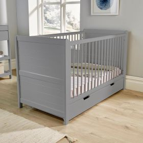Grey cot with adjustable base positions, slatted sides and a drawer underneath